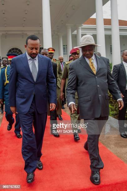 Ethiopia's Prime Minister Abiy Ahmed and Uganda's President Yoweri Museveni walk together during a welcome ceremony for his twoday state visit at...