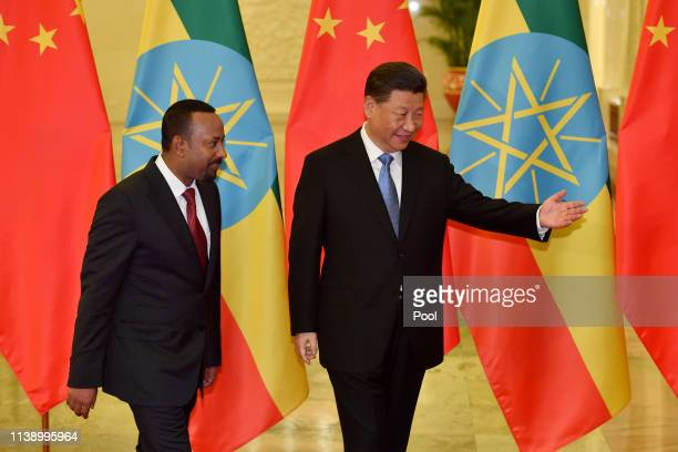 Ethiopia's Prime Minister Abiy Ahmed is shown the way by Chinese president Xi Jinping before their meeting at the Great Hall of the People in Beijing...