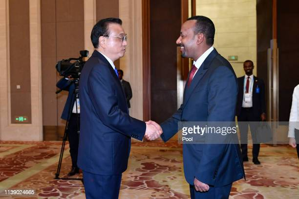 Ethiopia's Prime Minister Abiy Ahmed shakes hands with China's Premier Li Keqiang after their meeting at the Diaoyutai State Guesthouse on April 24...