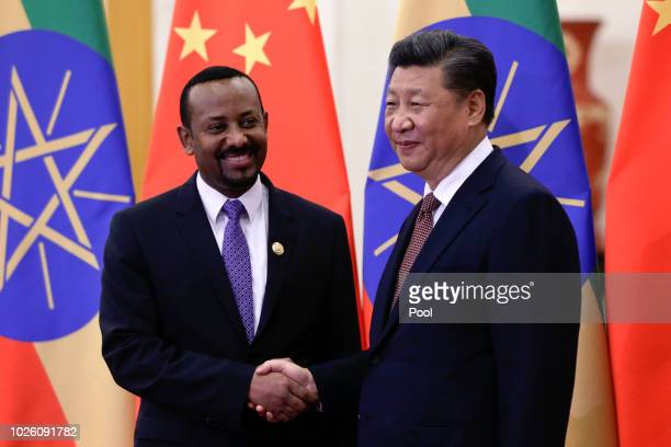 Ethiopia's Prime Minister Abiy Ahmed, shakes hands with Chinese President Xi Jinping before their bilateral meeting at the Great Hall of the People...