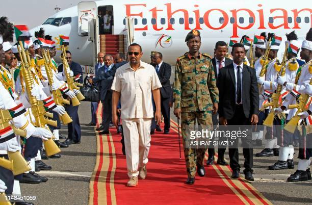 Ethiopia's Prime Minister Abiy Ahmed walks alongside Shams-Eddin Kabashi Sudan's Transitional Military Council spokesman upon his arrival at Khartoum...