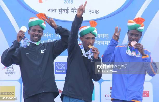 Ethiopia's Solomon Deksisa who won the Mumbai Marathon poses with second position Shumet Akalnaw of Ethiopia and Joshua Kipketer of Kenya at the...
