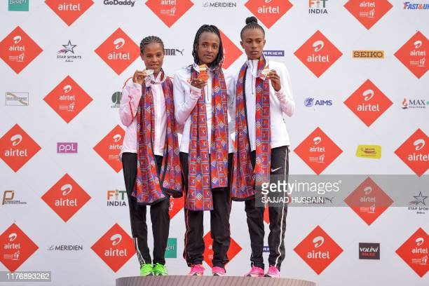 Ethiopia's Tsehay Gemechu poses with her gold medal along with her compatriots Yelamzerf Yehualaw with her silver medal and Zeineba Yimer with her...