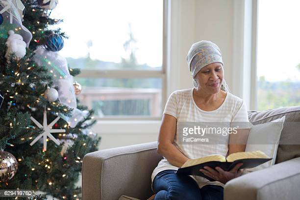 Ethnic adult female cancer patient reading by the Christmas tree