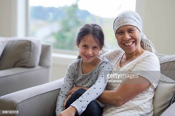 ethnic adult female cancer patient sitting with her granddaughter - tumeur nez photos et images de collection