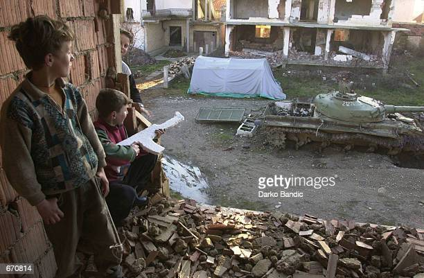 Ethnic Albanian boys play war games January 10 2001 in a Klina Kosovo neighborhood destroyed during the 1999 NATO bombing Controversy continues over...