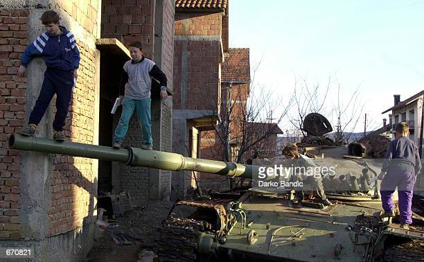 Ethnic Albanian boys play war games on a destroyed Yugoslav Army T55 tank January 10 2001 in Klina Kosovo The tank was destroyed during the 1999 NATO...