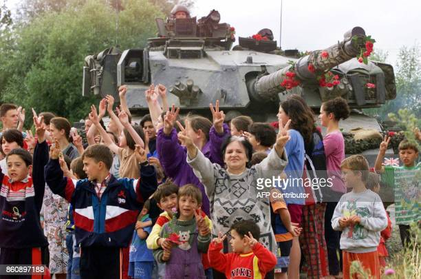 Ethnic Albanian people flash the victory sign and celebrate in front a British NATO tank, its gun barrel decorated with flowers, as the first NATO...