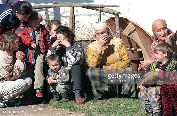 Ethnic Albanian women from the village of Donje Prekaze in the province of Kosovo cry as they hide themselves from Serbian police near a house close...