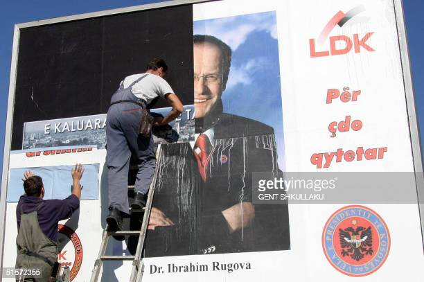 Ethnic Albanian workers remove an electoral poster of Kosovar President and leader of Democratic League of Kosovo Ibrahim Rugova in Pristina Kosovo...