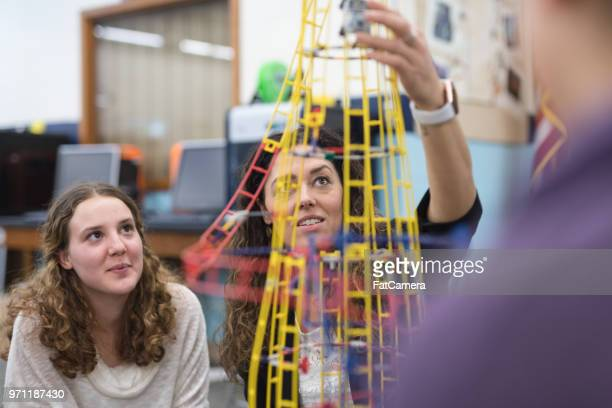 ethnic art teacher shows her class a colorful example of sculpture - physics stock pictures, royalty-free photos & images