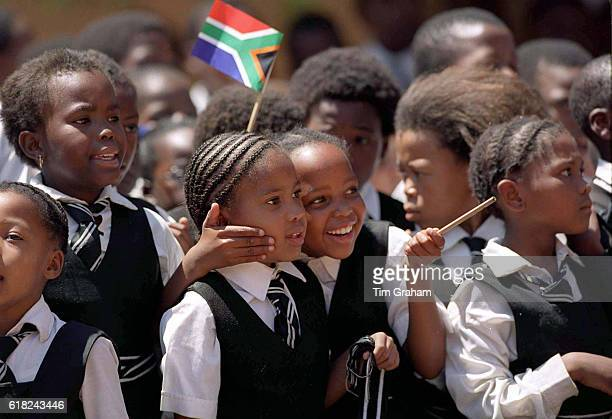 Ethnic black South African schoolchildren in school uniforms girls and boys wait for VIP in Alexandra Township Education Students Happy Affection...