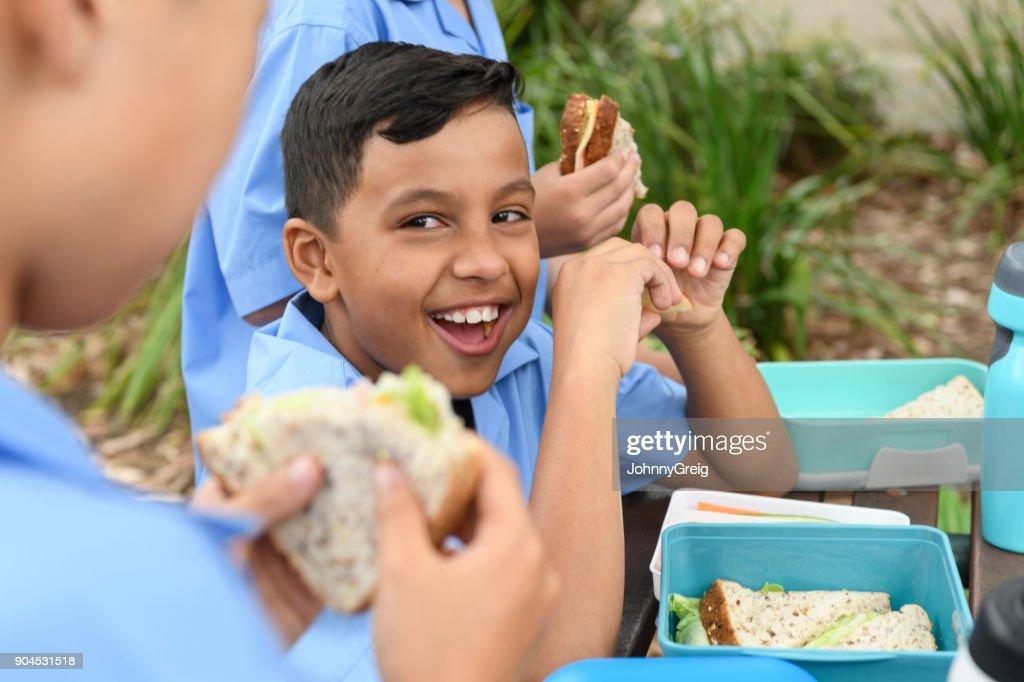 Etnia boy comer almuerzo fuera con amigos de la escuela : Foto de stock