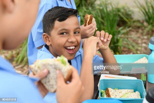 Ethnic boy eating packed lunch out side with school friends