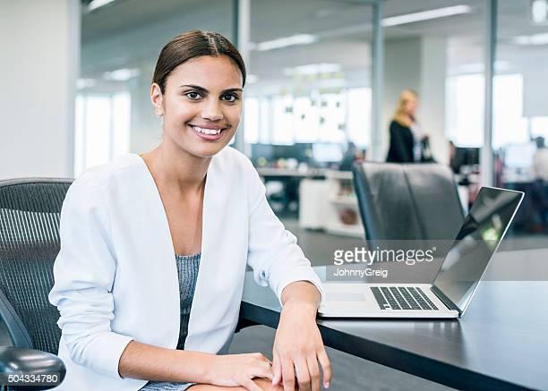 Étnica empresaria en escritorio con ordenador portátil en oficina moderna