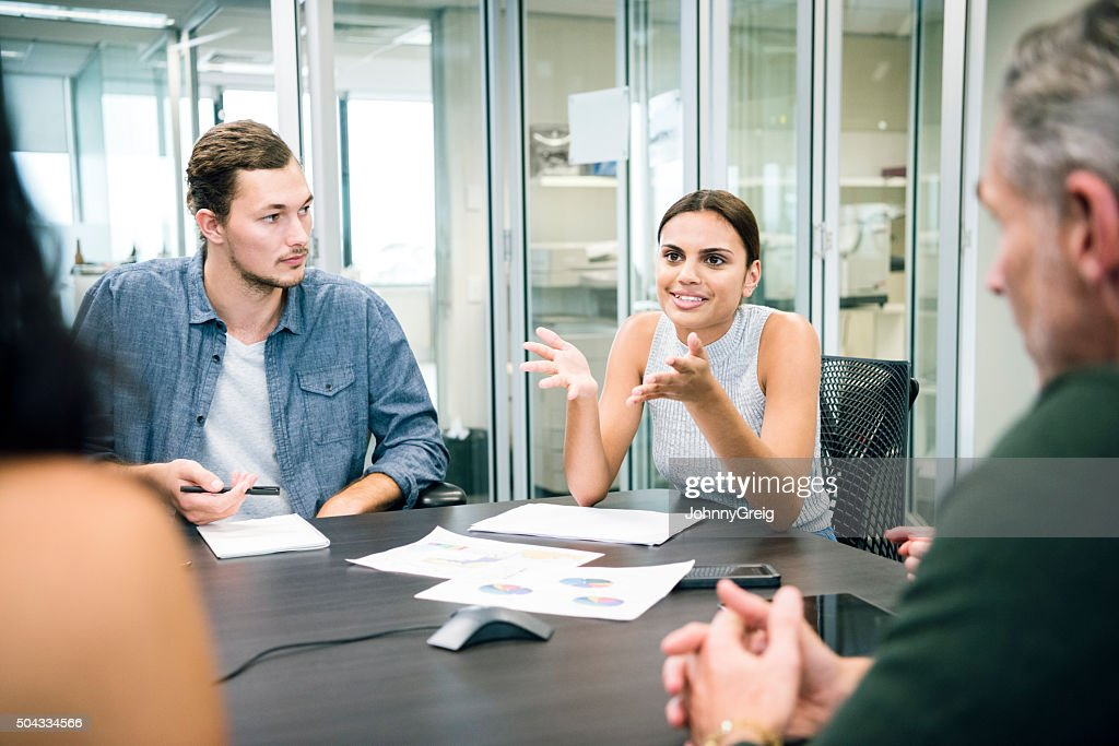 Ethnic businesswoman explaining to colleagues in business meeting : Stock Photo