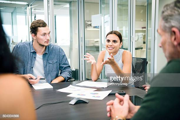 Ethnic businesswoman explaining to colleagues in business meeting