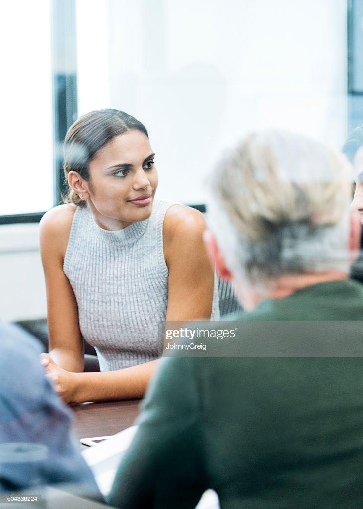 Ethnic businesswoman in business meeting looking away : Stock Photo