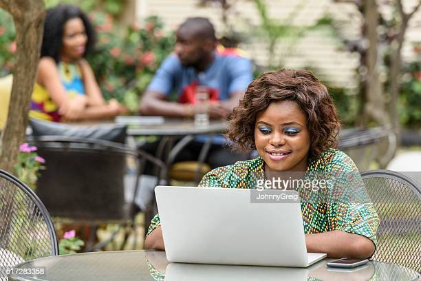 Ethnic businesswoman woman using laptop, smiling