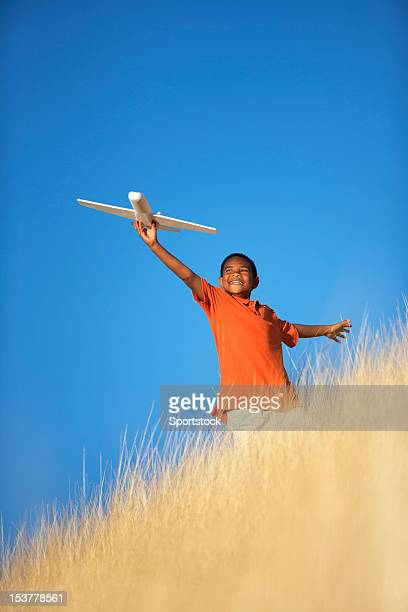 Ethnic Child Playing with Toy Glider Airplane in Field