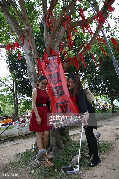 Ethnic Chinese girls take a selfie in front of the tree of hope as Chinese believes will bring blessing at the Fo Guang Shan Dong Zen Temple to...