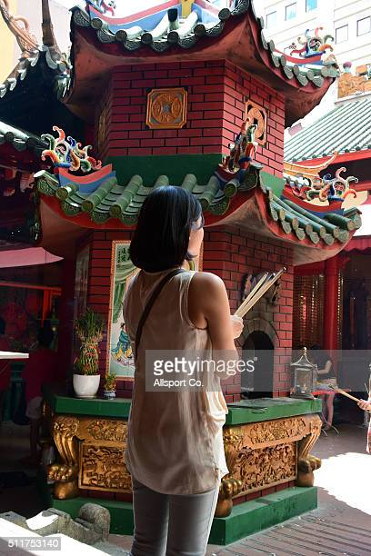 A ethnic Chinese woman offers prayers at a temple prior to celebrate the Lantern Festival on the last day of Chinese Lunar New Year celebrations The...