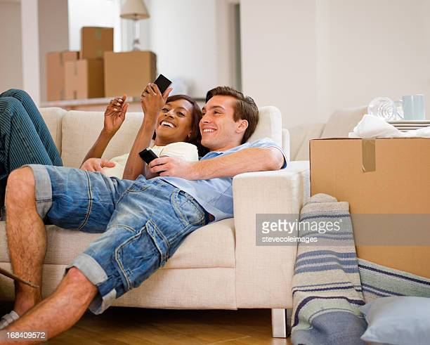 Ethnic Couple Relax on Sofa After Moving