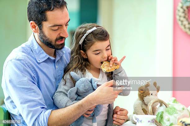 Ethnic dad holding plate while daughter eats a pastry