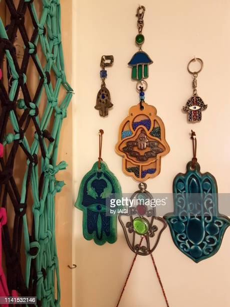 ethnic decors, a hamsa collection on the wall. jewish hamsa hands, good luck charms in the form of a hand, symbols of divine protection - hamsa symbol stock photos and pictures