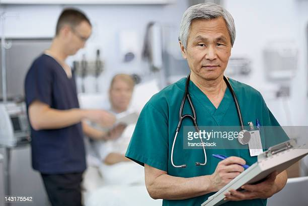 Ethnic Doctor Filling Out Patient Chart
