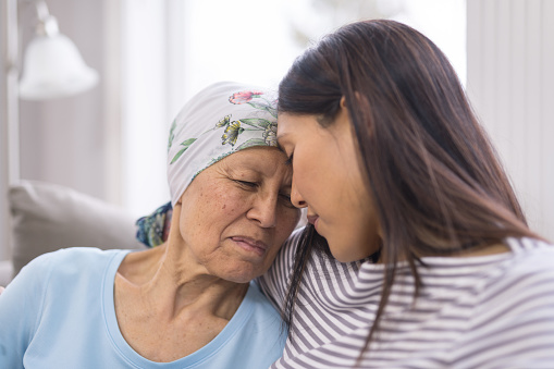 Ethnic elderly woman with cancer embracing her adult daughter 951679818