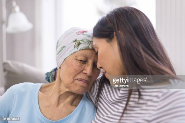 ethnic elderly woman with cancer embracing her adult daughter - care stock pictures, royalty-free photos & images