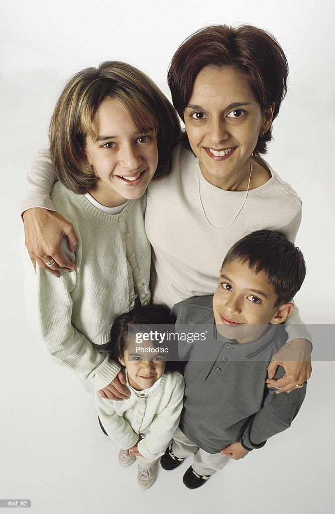 ethnic family mom with her arms around her three young kids : Foto de stock