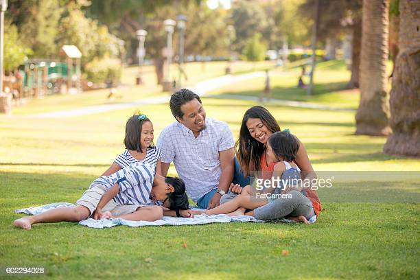 ethnic family with three children relaxing outdoors on a blanket - filipino culture stock pictures, royalty-free photos & images