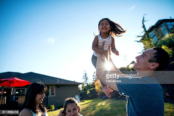 Ethnic father holding his daughter in the air