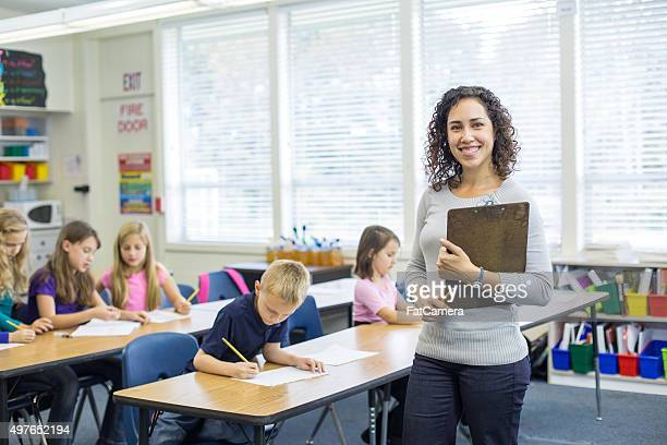 Ethnic female elementary teacher posing in front of classroom