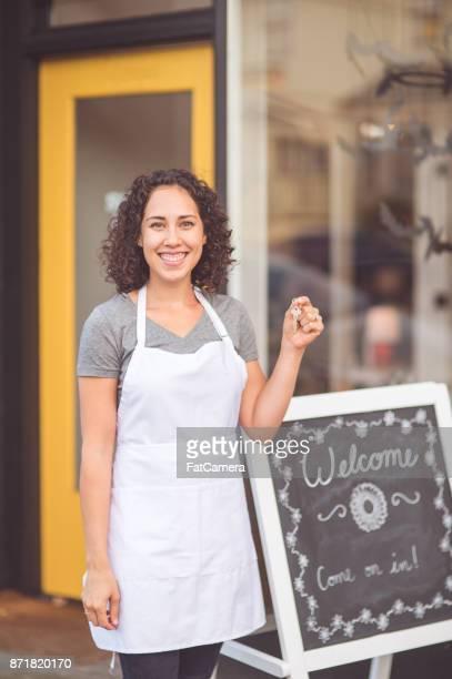 民族の女性起業家が彼女の新しい店の外に立っています。