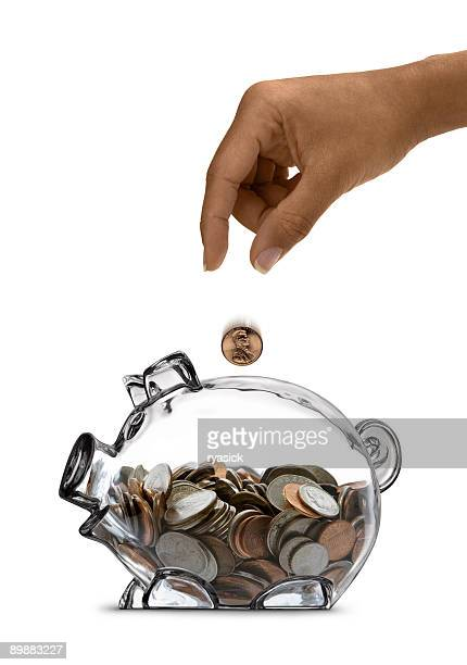 Ethnic Female Hand Drops Coin Into Half-filled Clear Piggy Bank