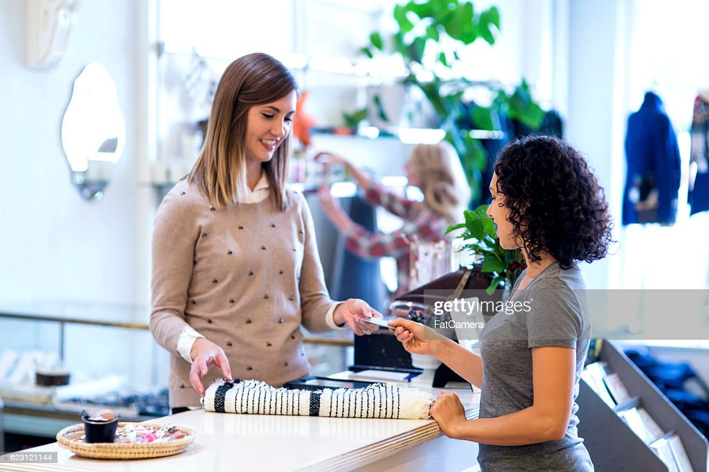 Ethnic female handing payment card over to female business owner : Stock Photo