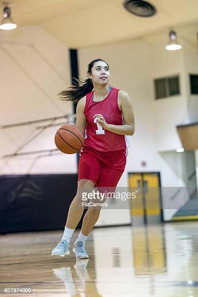 Ethnic female high school basketball player dribbling ball