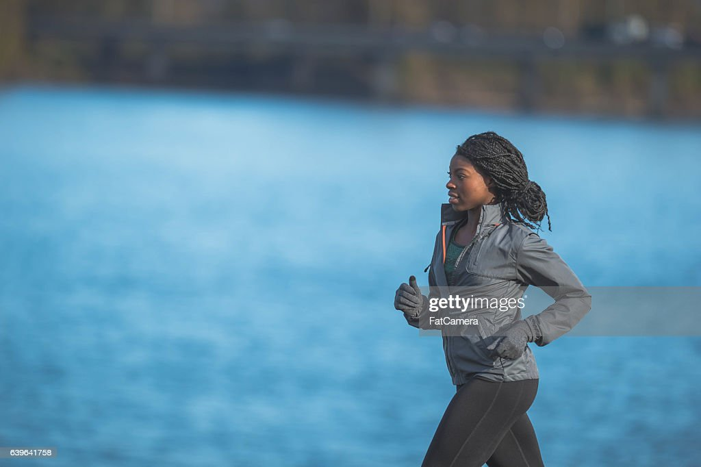 Ethnic female is focused while running and training outdoors : Stock Photo