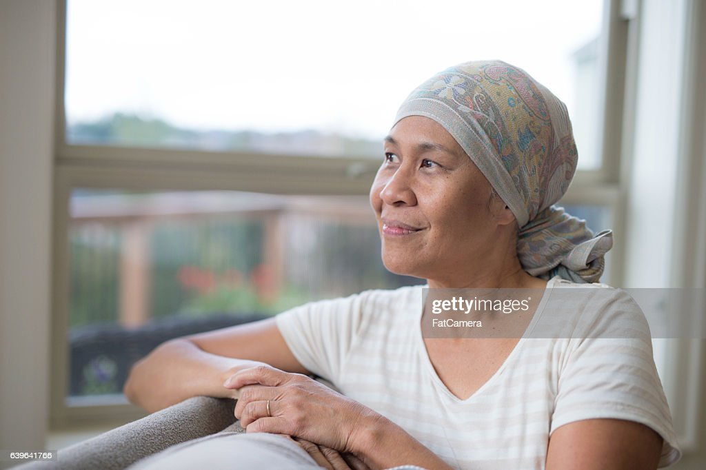 Ethnic female with cancer smiling and looking out the window : Stock Photo