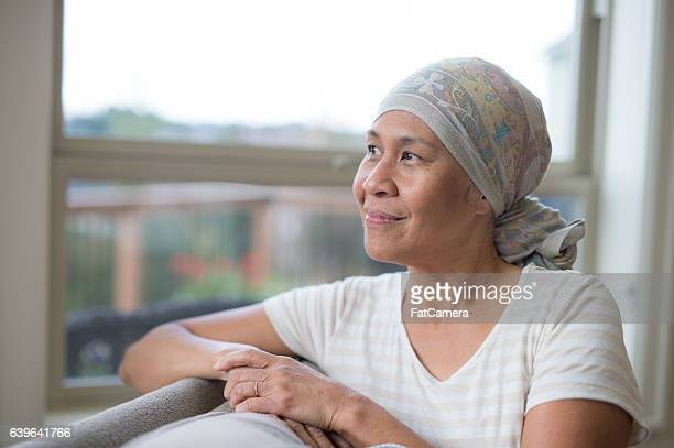 Ethnic female with cancer smiling and looking out the window