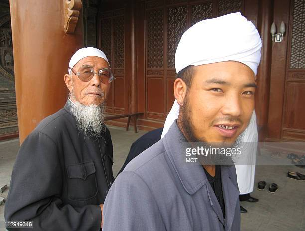 Ethnic Hui enter a mosque in Tongxin China for prayers The Hui are China's largest Muslim minority Hui men almost always wear a white cap or head...