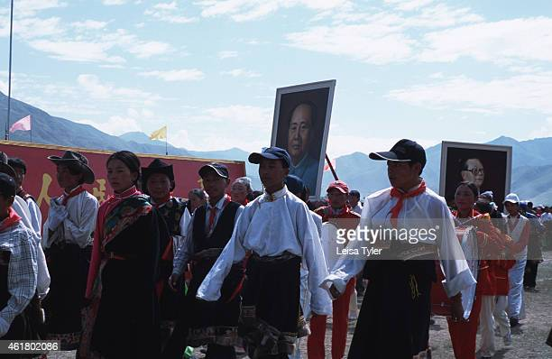Ethnic Khampa teenagers carrying posters of Chairman Mao Ze Dong and PM Jiang Ze Min at the opening ceremony of the Yushu Horseracing Festival in...