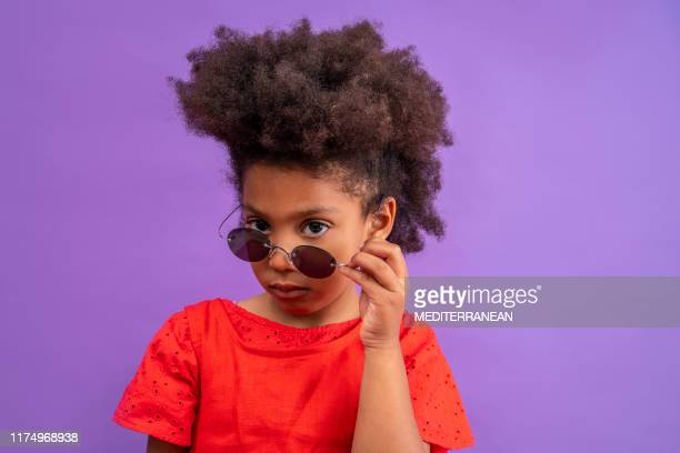 ethnic kid girl looking camera lowering sunglasses - attitude stock pictures, royalty-free photos & images