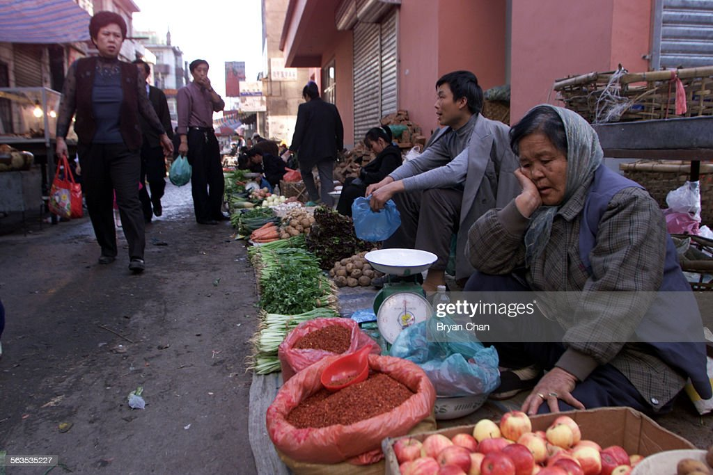 Ethnic Koreans shop and sell goods in an open–air market in