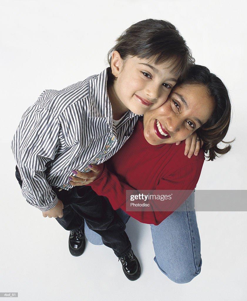 ethnic mom in red shirt kneels with daughter : Foto de stock