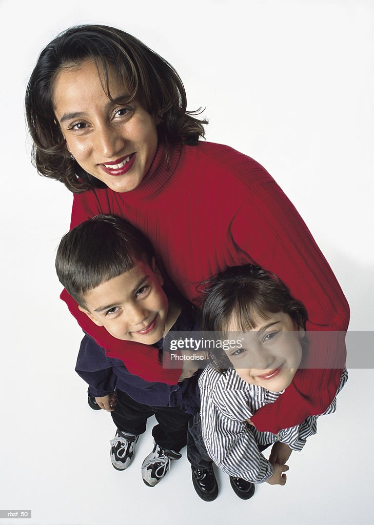 ethnic mom in red shirt stands behind two young kids with her arms around them : Foto de stock
