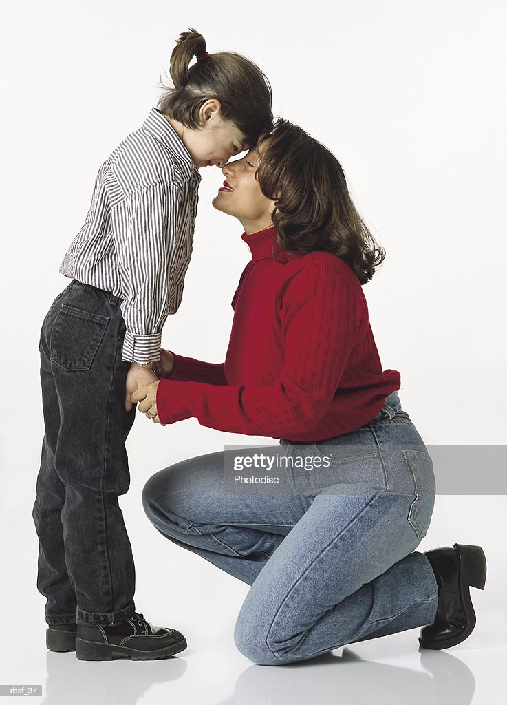 ethnic mom kneels while holding the hands of young daughter touching nose to nose : Foto de stock